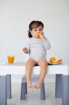 Sentado na mesa menina comendo laranja