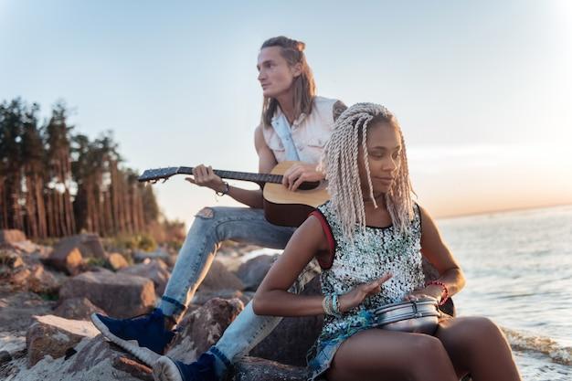 Sentado na rocha. homem loiro e atlético tocando violão enquanto está sentado em uma rocha perto da praia
