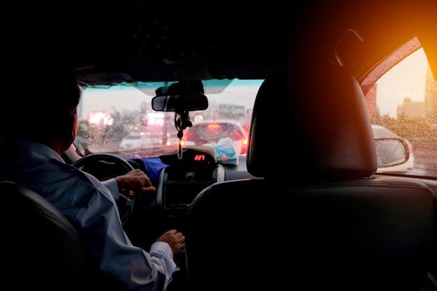 Sentado no banco de trás de um táxi com engarrafamento pesado em um dia chuvoso.