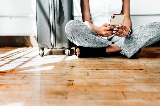 Sentado no chão usando smartphone