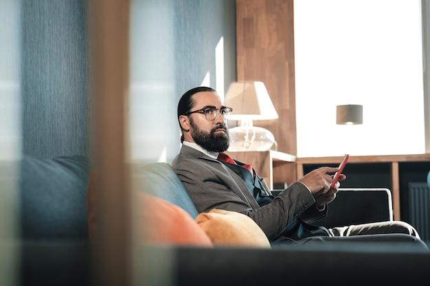 Sentado no sofá. homem barbudo, de olhos escuros, usando óculos, esperando seu parceiro de negócios sentado no sofá