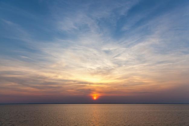 Sentado o sol contra o céu. o céu está se pondo.