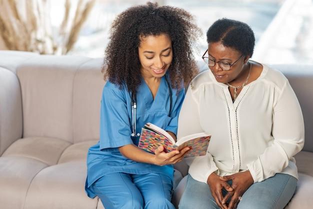 Sentado perto do paciente. jovem enfermeira carinhosa afro-americana sentada no sofá perto da paciente e lendo um livro para ela