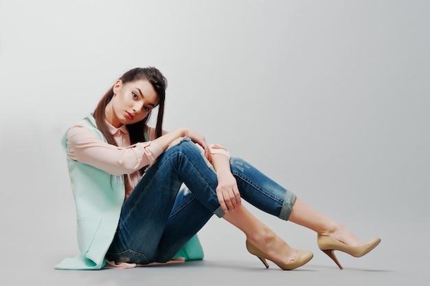 Sentado retrato morena jovem vestindo blusa rosa, jaqueta turquesa, jeans rasgados e sapatos creme sobre fundo cinza