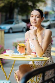 Sentado sozinho. mulher calma e relaxada sentada à mesa amarela do café ao ar livre e tocando seu queixo enquanto bebe limonada