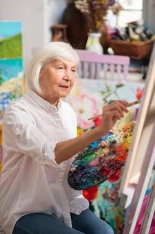 Sentar e pintar. vista superior de uma mulher loira idosa sentada perto de uma tela com paleta de cores