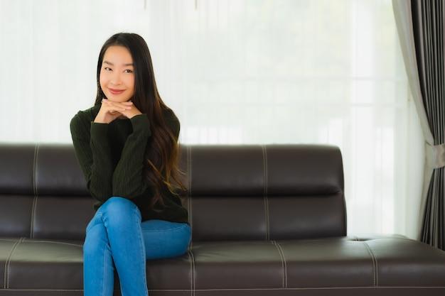 Sente-se jovem mulher asiática retrato bonito relaxar no sofá