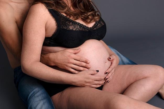 Sente-se mulher grávida está de mãos dadas com o marido na grande barriga. casal esperando um bebê em um fundo cinza.