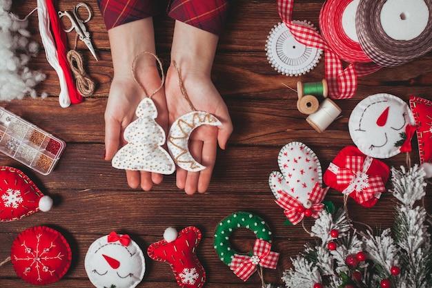 Senti as decorações de natal na mesa de madeira - mulher se preparando para fazer feito à mão