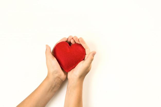 Senti o coração vermelho nas mãos da criança em branco