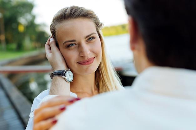 Sentimento de amor. mulher simpática e positiva olhando para o rosto do namorado enquanto está apaixonada por ele