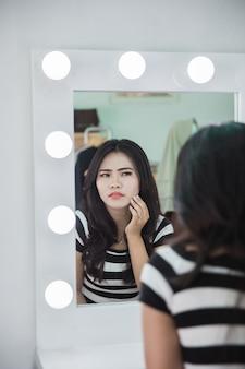 Sentimento infeliz ao olhar o rosto no espelho