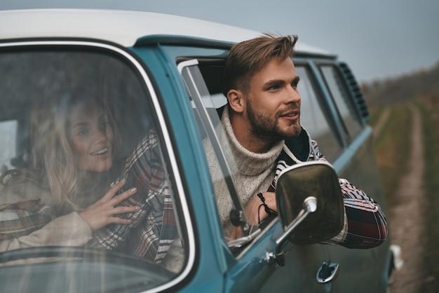 Sentimentos de tirar o fôlego? jovem bonito inclinando-se para fora da janela da van e sorrindo enquanto está sentado no banco do passageiro da frente com a namorada