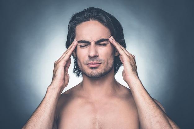 Sentindo aquela terrível dor de cabeça. retrato de um jovem frustrado sem camisa, mantendo os olhos fechados e tocando a cabeça com os dedos em pé contra um fundo cinza
