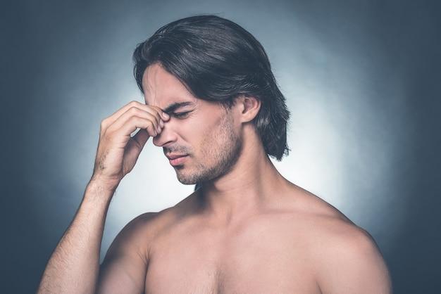 Sentindo estressado. retrato de um jovem frustrado sem camisa, mantendo os olhos fechados e massageando o nariz em um fundo cinza