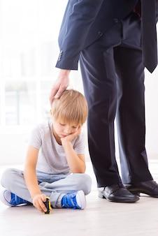 Sentindo falta de seu pai ocupado. menino triste segurando a mão no queixo enquanto brinca com o carrinho de brinquedo, enquanto o pai em trajes formais o consola