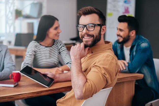 Sentindo-me confiante na minha equipe. grupo de empresários em roupas casuais inteligentes discutindo algo enquanto um homem segurando um tablet digital e olhando por cima do ombro com um sorriso