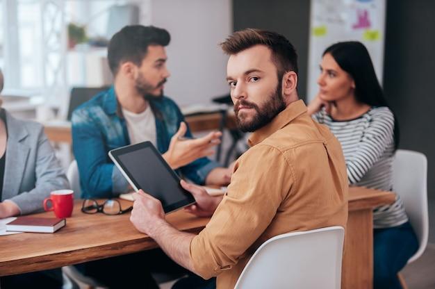 Sentindo-me confiante na minha equipe. grupo de empresários em roupas casuais inteligentes discutindo algo enquanto um homem segurando um tablet digital e olhando por cima do ombro