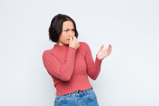 Sentindo nojo, segurando o nariz para evitar cheirar um fedor sujo e desagradável