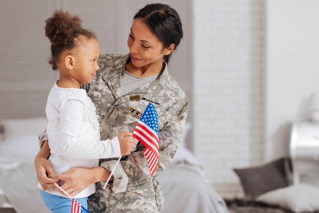 Sentindo o espírito. jovem linda e corajosa contando à filha sobre o serviço prestado enquanto a abraçava depois de algumas semanas sem vê-la