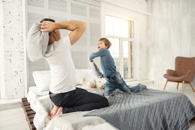 Sentindo ótimo. menino alegre de cabelos louros sorrindo e brincando com o papai em casa e eles brigando de travesseiros