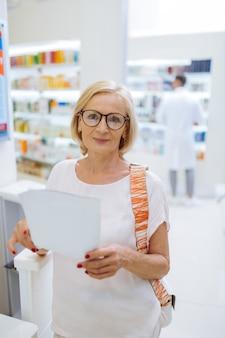 Sentindo-se bem. loira fofa do sexo feminino com um sorriso no rosto enquanto segura uma receita médica Foto Premium