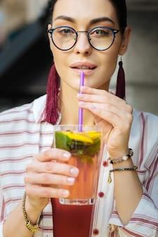 Sentindo-se bem. mulher bonita e calma sorrindo e saboreando sua limonada enquanto bebe com canudinho