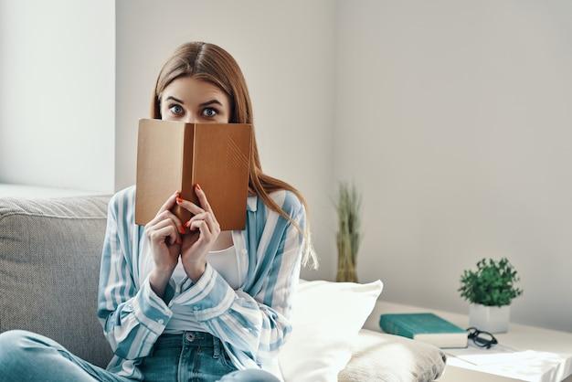 Sentindo-se brincalhão. mulher jovem e atraente olhando para a câmera e cobrindo o rosto com um livro, enquanto passa um tempo em casa