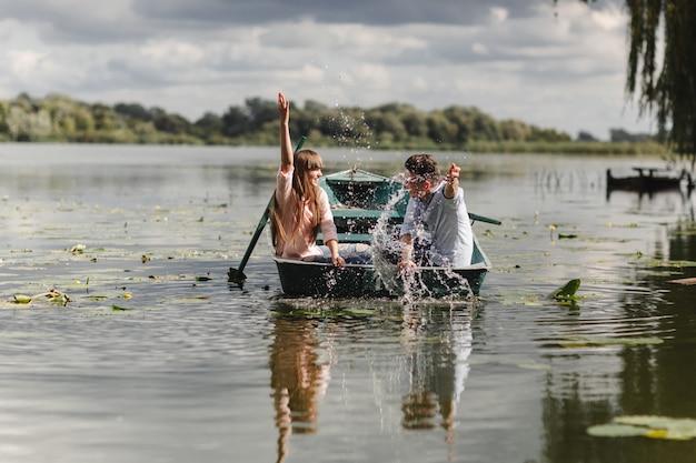 Sentindo-se brincalhão. pares novos bonitos que apreciam a data romântica ao enfileirar um barco.