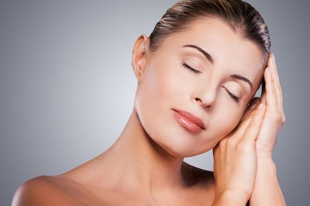 Sentindo-se calmo e fresco. retrato de uma mulher madura sem camisa, mantendo os olhos fechados e tocando o rosto com as mãos em um fundo cinza