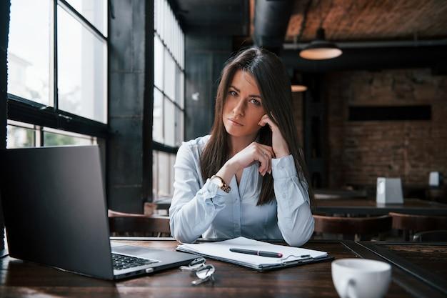 Sentindo-se calmo. mulher de negócios com roupas oficiais está dentro de casa no café durante o dia.