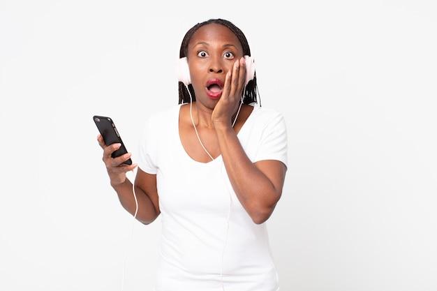 Sentindo-se chocado e assustado com fones de ouvido e um smartphone