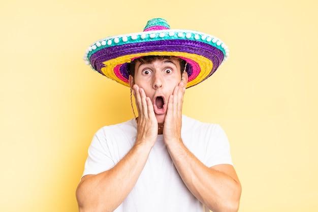 Sentindo-se chocado e assustado, parecendo aterrorizado com a boca aberta e as mãos nas bochechas. conceito de chapéu mexicano