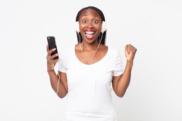 Sentindo-se chocado, rindo e comemorando o sucesso com fones de ouvido e um smartphone