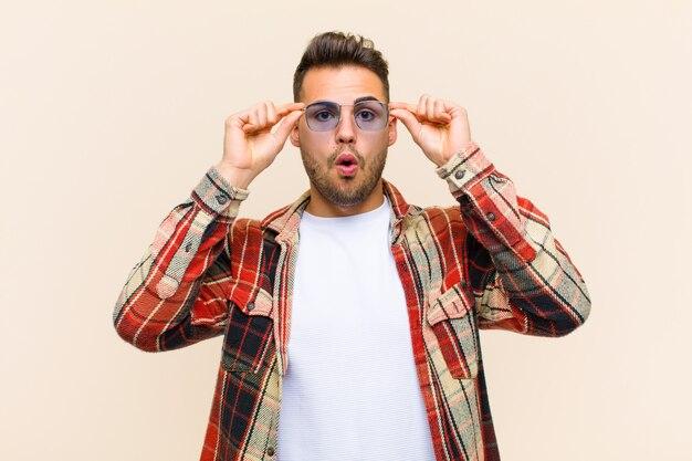 Sentindo-se chocado, surpreso e surpreso, segurando os óculos com um olhar atônito e incrédulo
