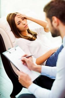 Sentindo-se desesperado e deprimido. mulher deprimida sentada na cadeira com a mão na cabeça enquanto o jovem sentado perto dela e escrevendo algo em sua prancheta