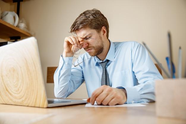 Sentindo-se doente e cansado. homem jovem doente infeliz triste frustrado massageando sua cabeça enquanto está sentado em seu local de trabalho no escritório.