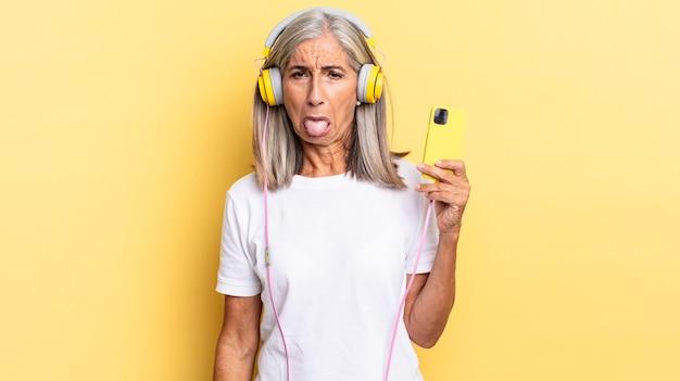 Sentindo-se enojado e irritado, mostrando a língua, não gostando de algo nojento e nojento com fones de ouvido