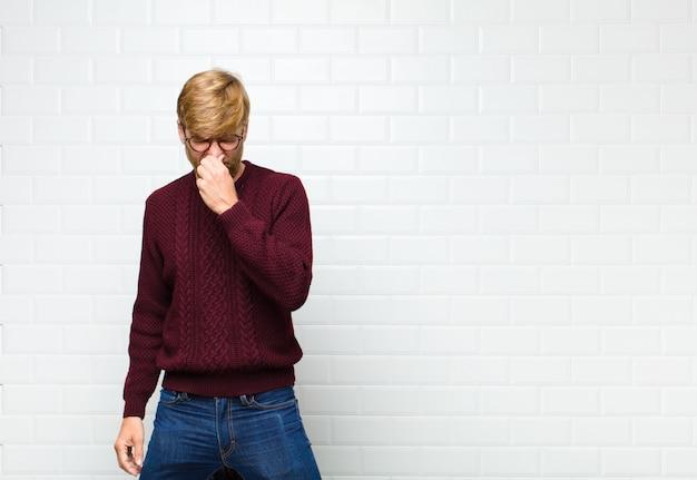 Sentindo-se enojado, segurando o nariz para evitar cheirar um fedor desagradável e desagradável