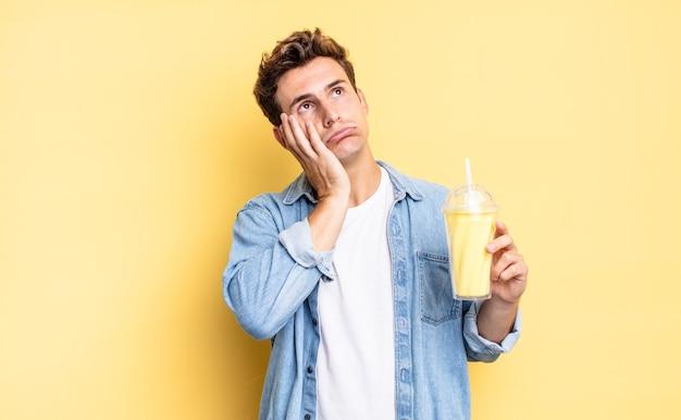 Sentindo-se entediado, frustrado e com sono depois de uma tarefa cansativa, enfadonha e tediosa, segurando o rosto com a mão. conceito de milkshake
