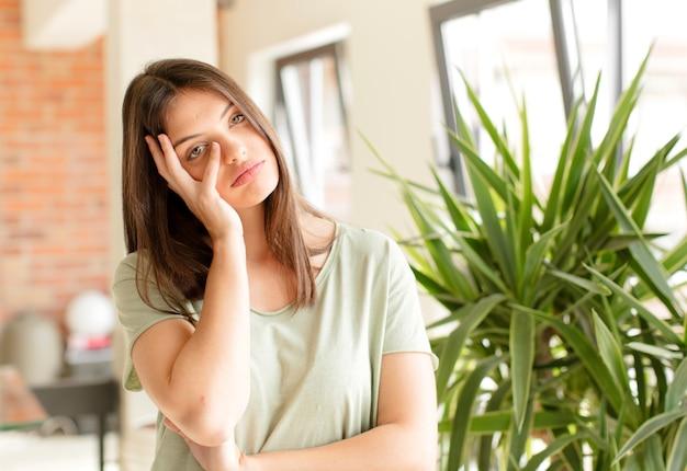 Sentindo-se entediado, frustrado e com sono depois de uma tarefa enfadonha e entediante segurando o rosto com a mão