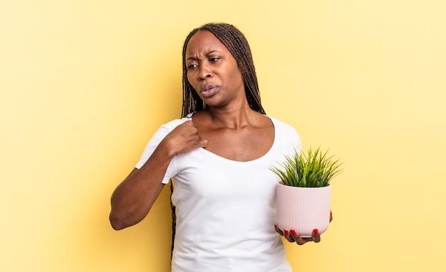 Sentindo-se estressado, ansioso, cansado e frustrado, puxando a gola da camisa, parecendo frustrado com o problema de segurar um vaso de planta