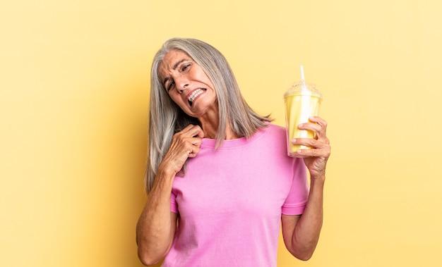 Sentindo-se estressado, ansioso, cansado e frustrado, puxando a gola da camisa, parecendo frustrado com o problema e segurando um milkshake