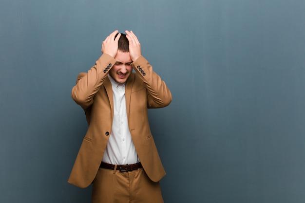 Sentindo-se estressado e ansioso, deprimido e frustrado com dor de cabeça, levantando as duas mãos