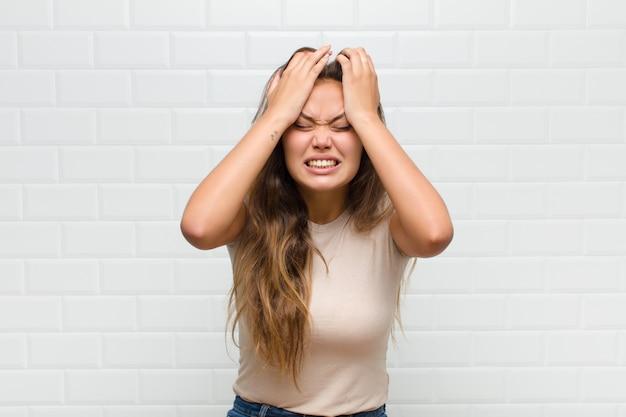 Sentindo-se estressado e ansioso, deprimido e frustrado com uma dor de cabeça, levando ambas as mãos à cabeça