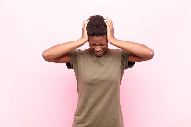 Sentindo-se estressado e frustrado, levantando as mãos na cabeça, cansado, infeliz e com enxaqueca