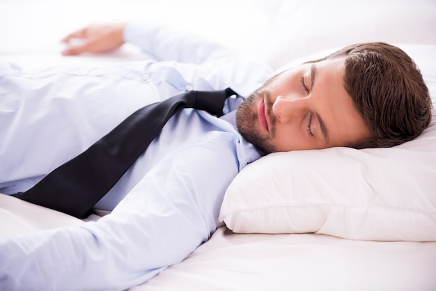 Sentindo-se exausto após um dia de trabalho. jovem bonito de camisa e gravata dormindo na cama