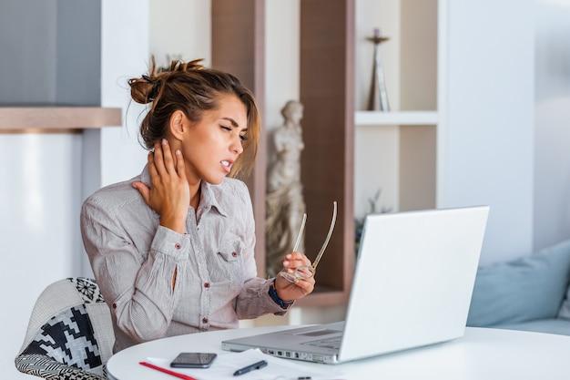 Sentindo-se exausto. jovem frustrada olhando exausta e massageando o pescoço enquanto está sentado no seu local de trabalho