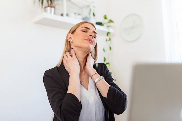 Sentindo-se exausto. mulher jovem frustrada parecendo exausta e massageando o pescoço enquanto está sentada no local de trabalho