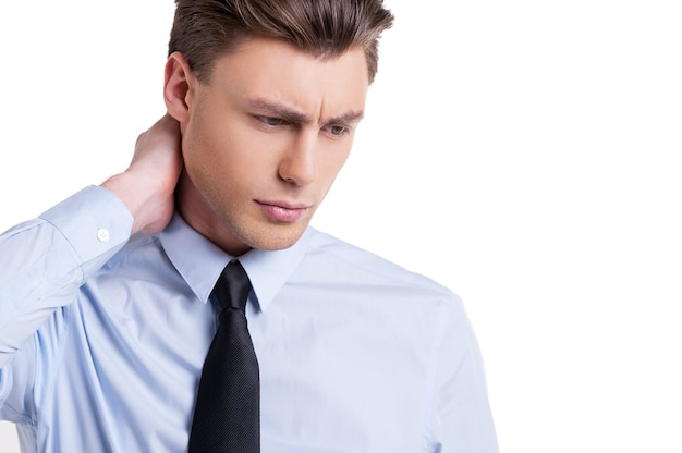 Sentindo-se exausto. retrato de jovem frustrado de camisa e gravata tocando seu pescoço e olhando para baixo em pé isolado no branco